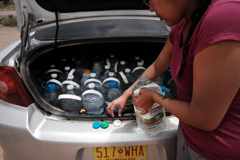A woman takes big bottle of water out of a car trunk full of plastic water bottles.