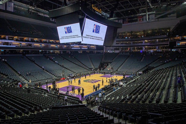 A near-empty basketball court with a Jumbotron overhead broadcasting the NBA logo.
