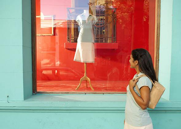 Young woman looking in shop window, side view.