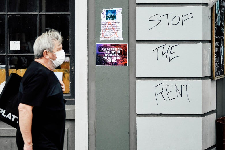 A man walks past a sign saying Stop the Rent on King Street in Newtown in Sydney, Monday, March 23, 2020. The state of NSW is shutting down all non-essential services to slow the rapidly spreading.