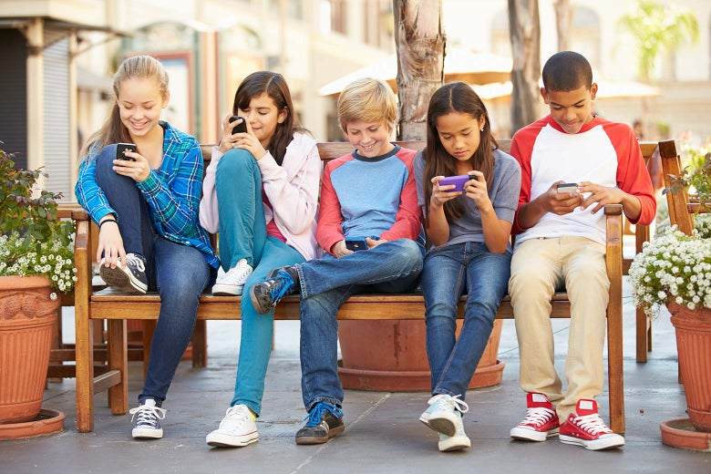 Kids sit on a bench and look at their smartphones.