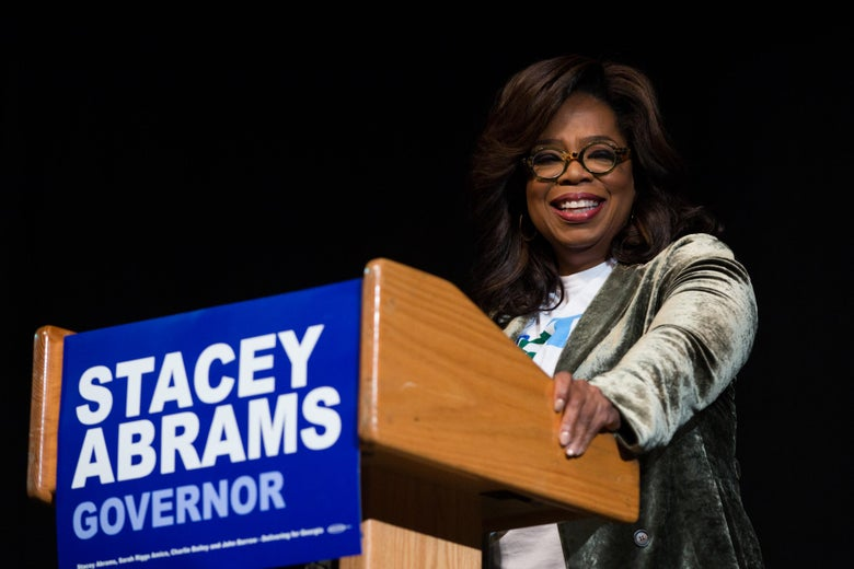 Oprah stands behind a podium with a Stacey Abrams sign on it.
