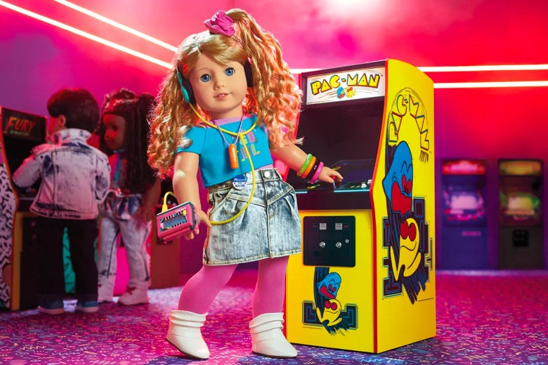 A doll wearing a denim skirt, crop top, Walkman, and side ponytail in front of a Pac-Man arcade game.