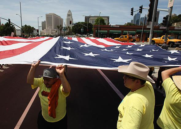 People carry a huge American flag in a march to the Metropolitan Detention Center during one a several May Day.