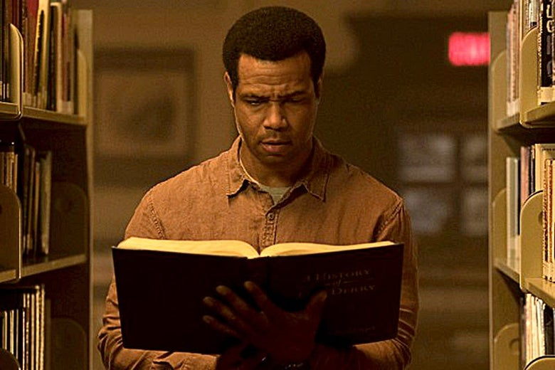 Isaiah Mustafa holding a book in a library in It: Chapter Two.