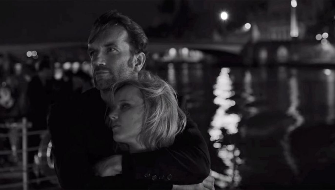 A man hugs a woman to his chest. The image is greyscale.