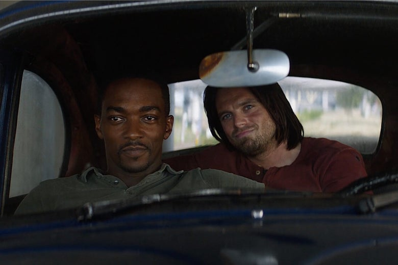 Falcon and Winter Solider sit smiling in a car together.