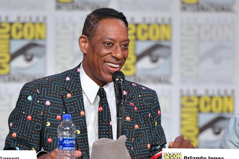 Orlando Jones, wearing a suit jacket with a Pac-Man maze on it, sits at a panel table before a Comic-Con logo backtrop, smiling broadly.