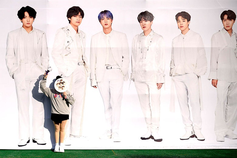 A fan poses for photos in front of a large image of BTS