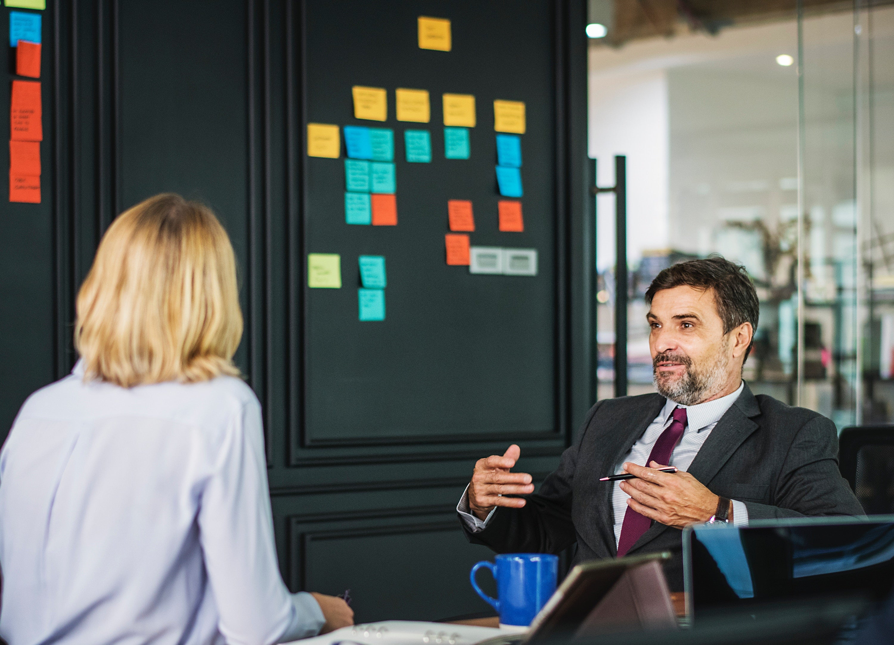A man talks to a woman in front of drawing board with multicolored sticky notes on t.