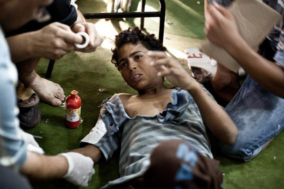 A wounded boy is treated as he lies on the floor of the Taamin Sehi field hospital during clashes between security officers and supporters of ousted president Mohamed Morsi, in downtown Cairo.