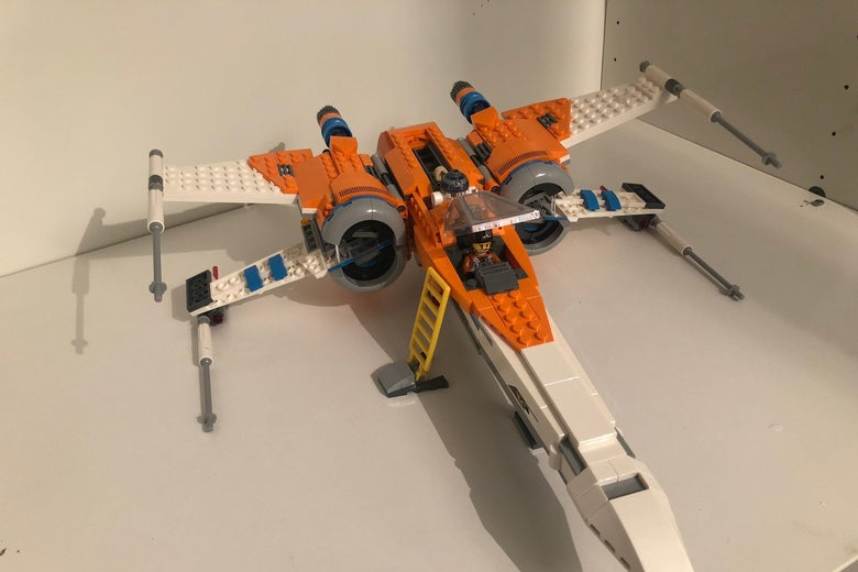 A Lego X-Wing sits on a table, complete, and immaculate