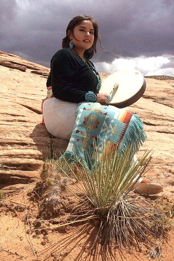 Nichele Yazzie in an arid landscape with dark clouds behind her.