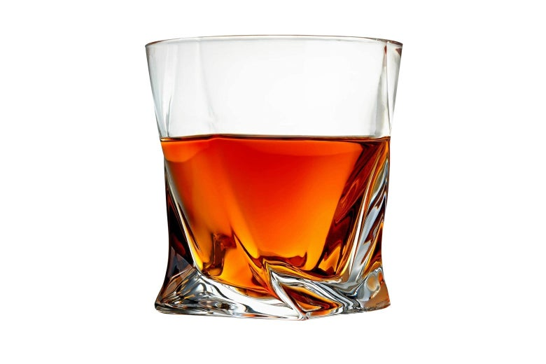 A glass with whiskey in it.