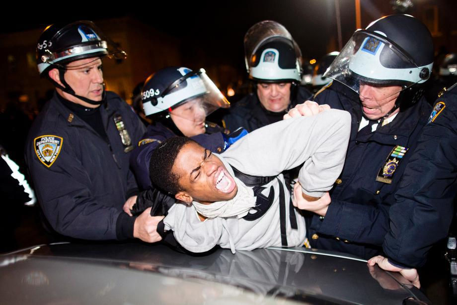 """Police officers arrest a demonstrator during a march after a vigil held for Kimani """"Kiki"""" Gray in the East Flatbush neighborhood of Brooklyn on March 13, 2013, in New York."""