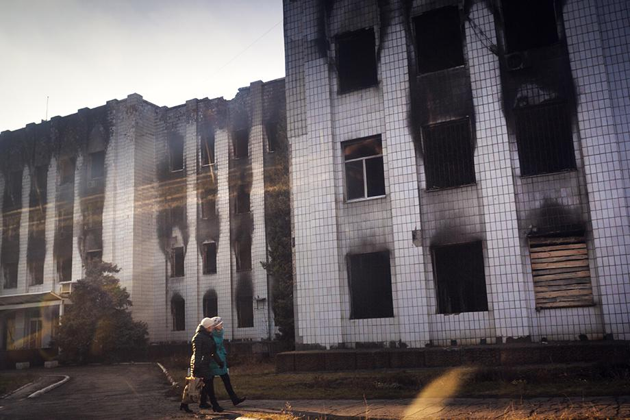 Two women pass the government building of Shakhtarsk, which was put on fire last spring.