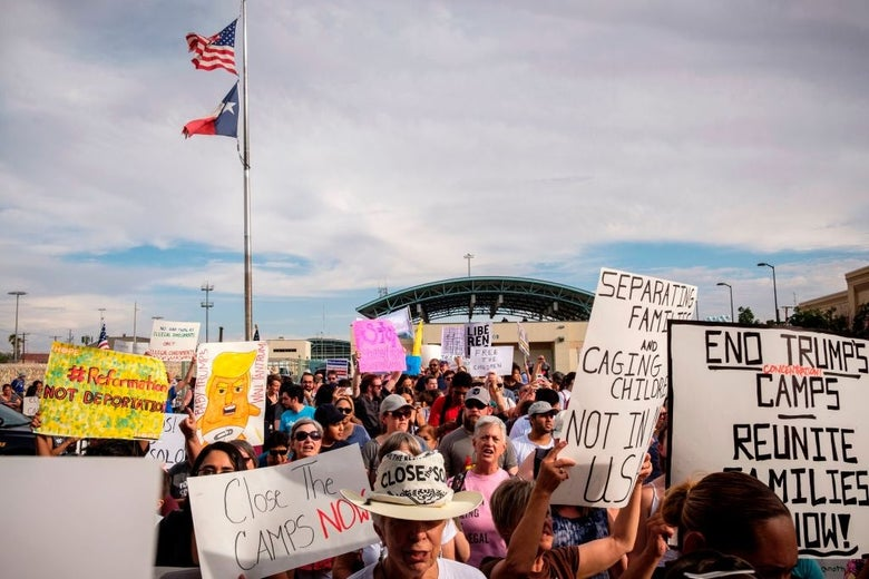 """Protesters carry signs with messages such as """"End Trump's Camps"""" in front of a border crossing station above which the American and Texan flags are raised."""