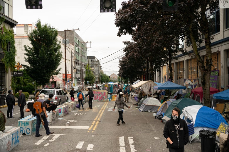 People walk around a street lined with tents.