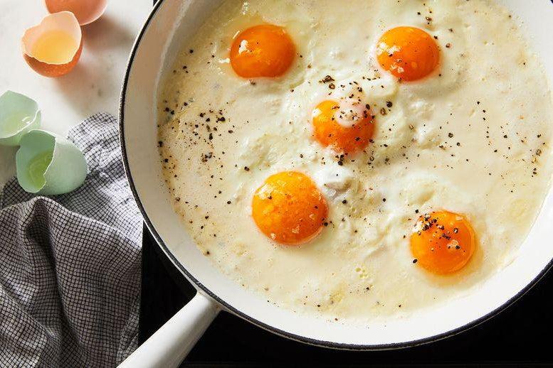 In a skillet, five orange egg yolks float in a sea of white liquid.