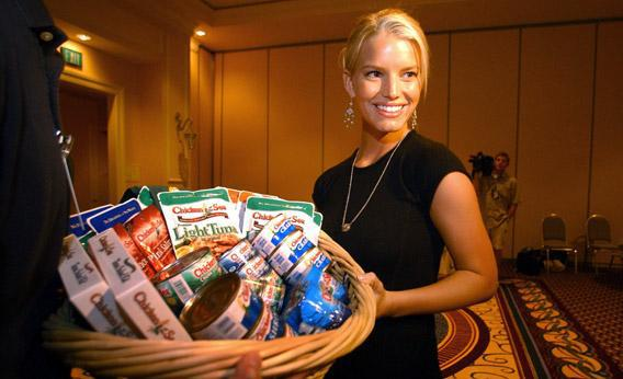 Pop star Jessica Simpson stands with a basket of tuna products during a visit to a Chicken of the Sea conference in 2003.