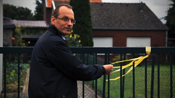 Dirk Jansen ties a yellow ribbon around a fence.