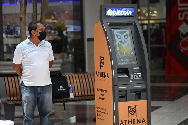 A man stands next to a Bitcoin ATM at a shopping mall in San Salvador.