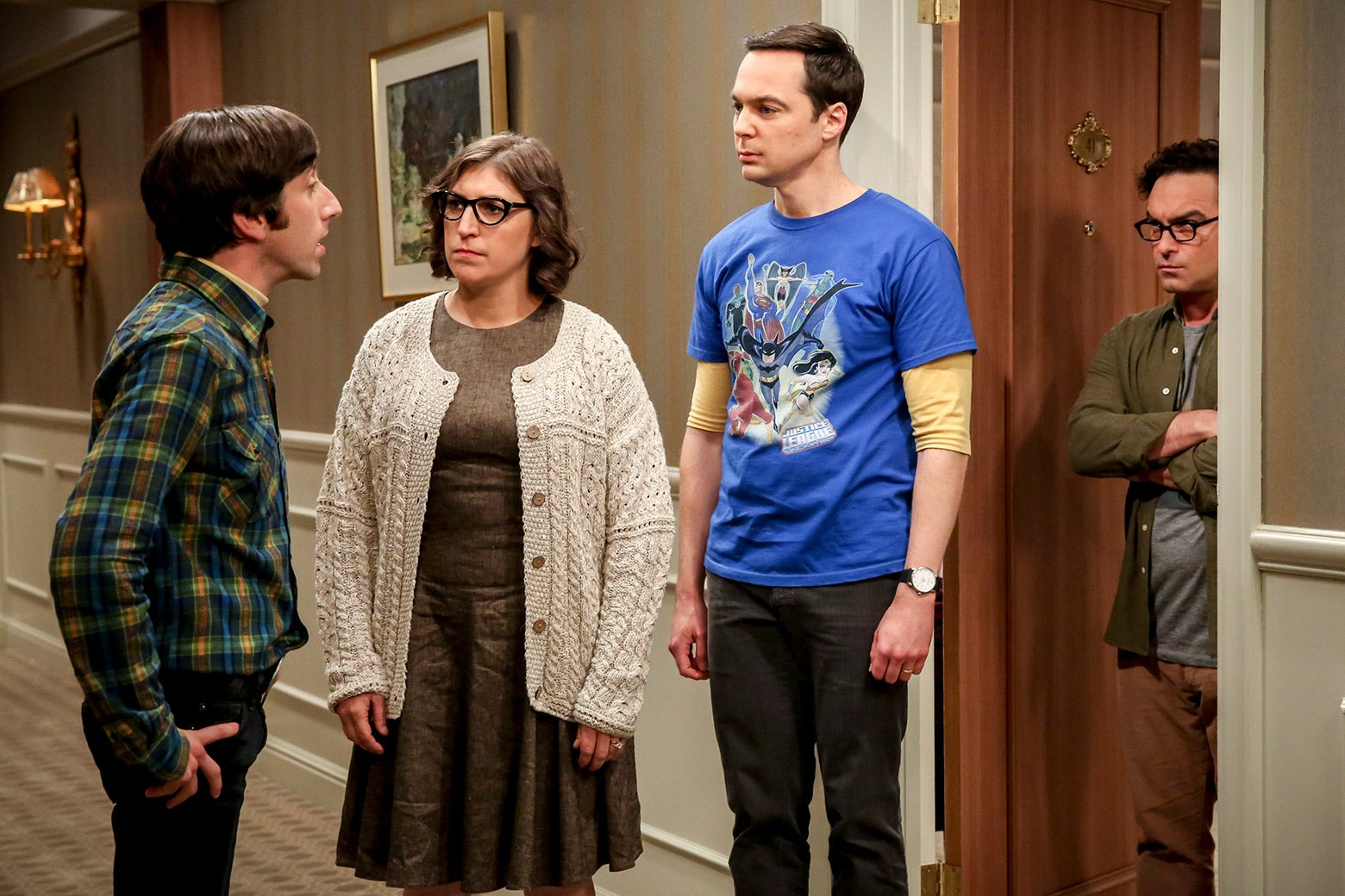 Simon Helberg, Mayim Bialik, Jim Parsons, and Johnny Galecki stand in a hallway in a still photo from the show.