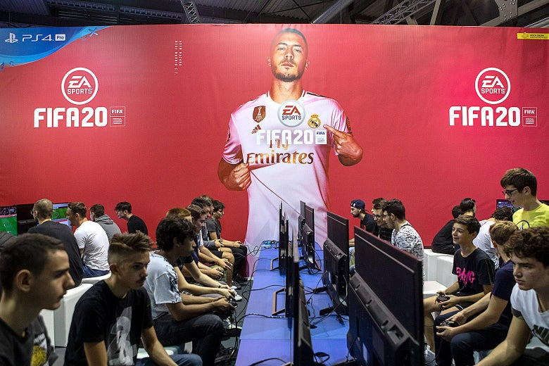 Gamers sit at rows of computers. A picture of a FIFA player along with the FIFA and EA logos is seen over them.