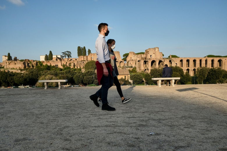 People wearing a protective face mask walk along the Circus Maximus (Circo Massimo) ancient Roman chariot-racing stadium, with the Temple of Apollo Palatinus (Tempio di Apollo Palatino, Rear) in Rome on November 11, 2020, during the government's restriction measures to curb the spread of COVID-19 novel coronavirus. - Italy has shut bars, restaurants and shops in the worst-affected areas and introduced a nationwide night curfew, but has so far swerved a second shutdown, with the antigen tests becoming a crucial part of its efforts. (Photo by ANDREAS SOLARO / AFP) (Photo by ANDREAS SOLARO/AFP via Getty Images)