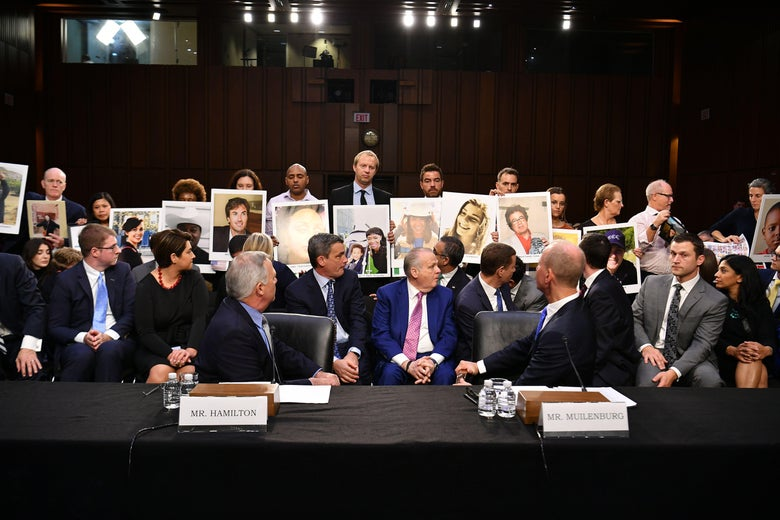 Boeing executives and other attendees of the committee hearing turn to face family members who hold up photos of Boeing 737 Max crash victims