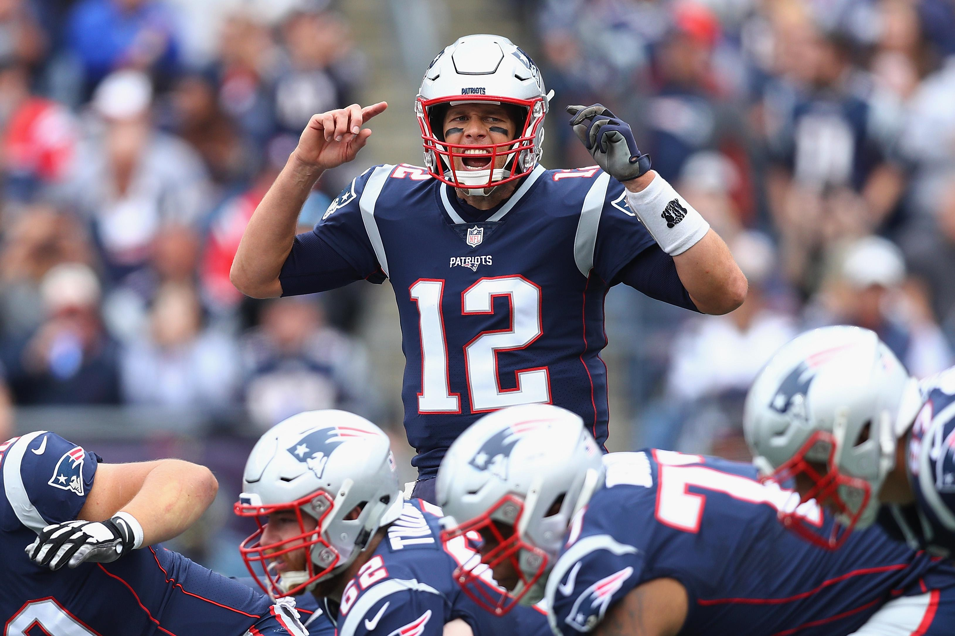 Tom Brady gestures at the line of scrimmage during an NFL game.