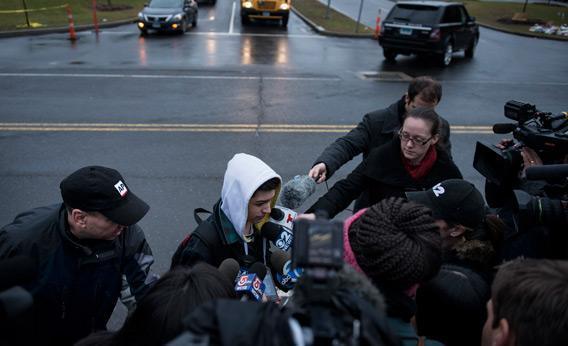 Reporters interview Newtown High School sophomore Tate Schwab while he walks to school on December 18, 2012 in Newtown, Connecticut.