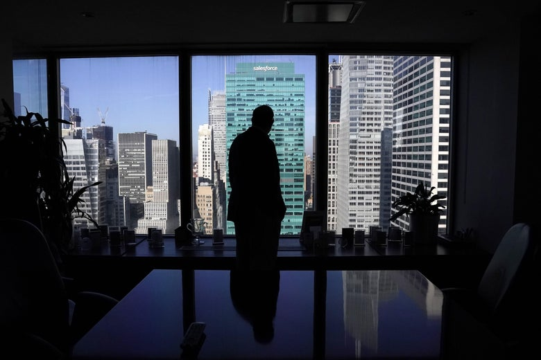 A man in a suit stands backlit in front of a window in an empty office overlooking Fifth Avenue buildings.