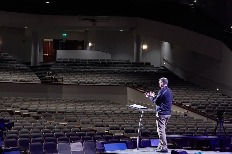 Troy Dobbs speaks at a podium before an empty auditorium.