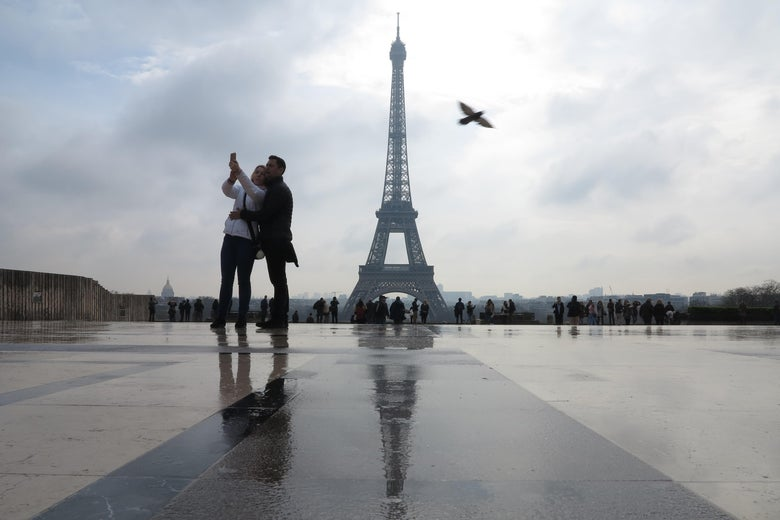A couple takes a selfie in front of the Eiffel tower in Paris.