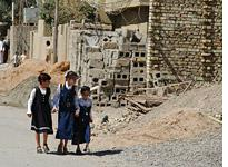 Schoolgirls hurry by the site of a torture house in Jolan, Fallujah. Click image to expand.