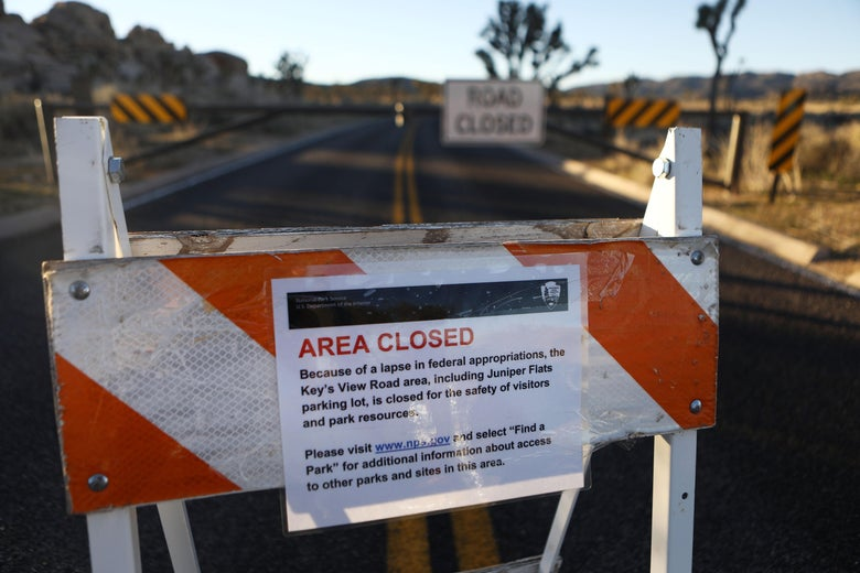 An 'Area Closed' sign is posted in front of a closed section of road at Joshua Tree National Park.
