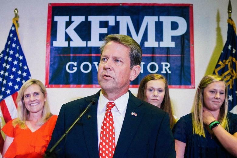Brian Kemp at a podium with family behind him.
