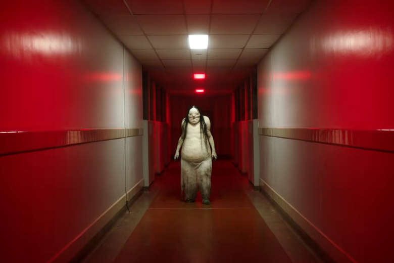A monsterous figure standing in a dim red lit hallway, in a still from the film adaptation of Scary Stories.