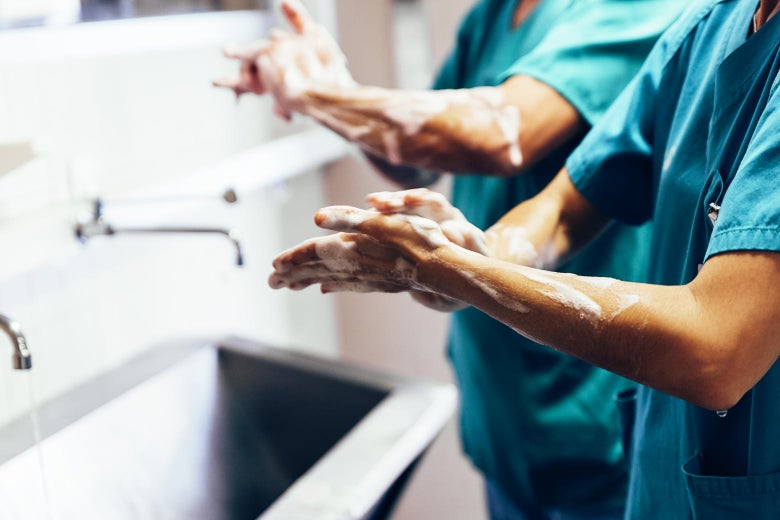 Health professionals wash their hands.