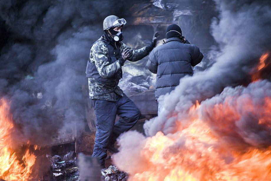 Demonstrators stand among the smoke of burning barricades during clashes with riot police in Kiev on Feb. 18, 2014.