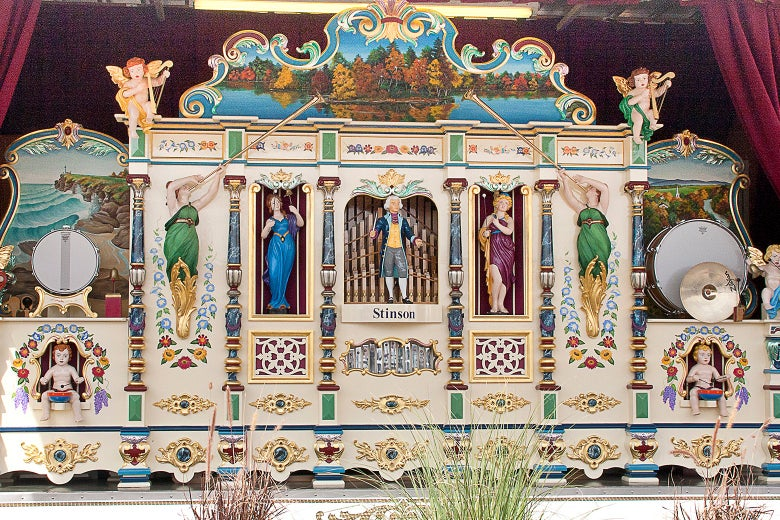 An elaborate fairground organ decorated with cherubs and statues of musicians.