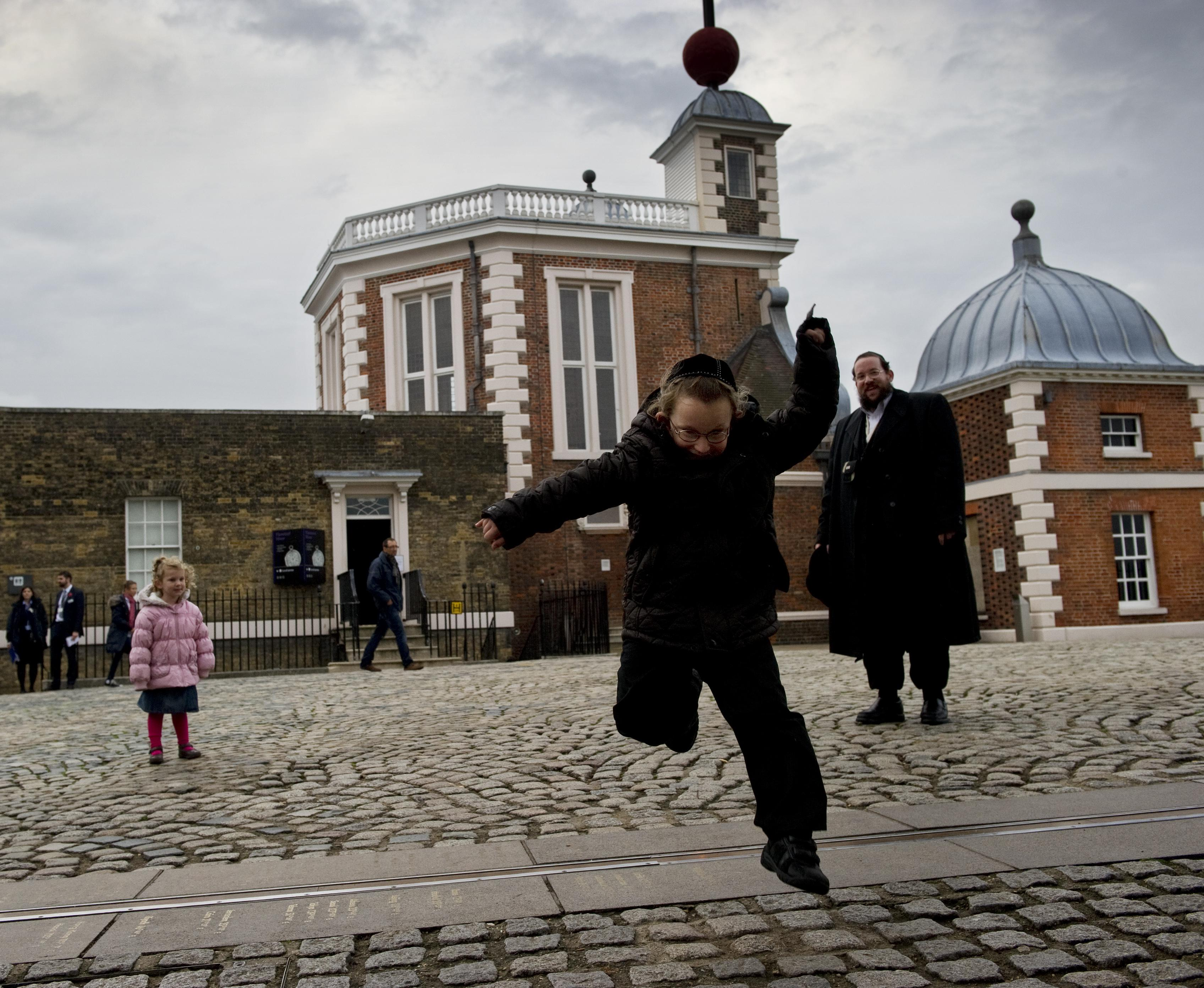 A tourist jumps over the Prime Meridian line at the Royal Observatory in Greenwich, London.