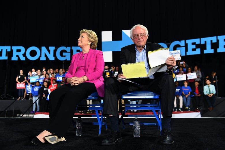 Hillary Clinton and Bernie Sanders sit on chairs looking away from one another during a campaign rally. Bernie is looking at sheets of notes.