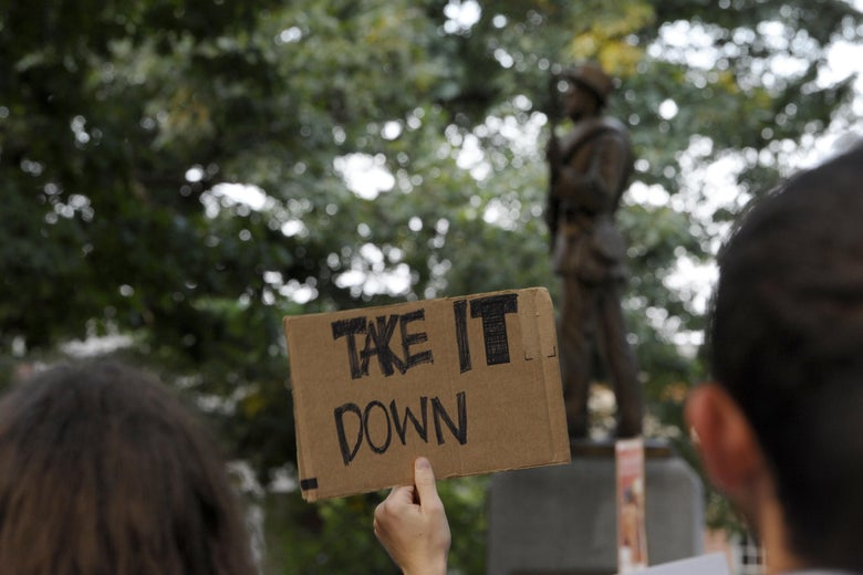 "A man holds a sign that says ""Take it down."" Silent Sam is seen in the background."