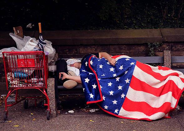 A homeless man sleeps under an American Flag blanket.