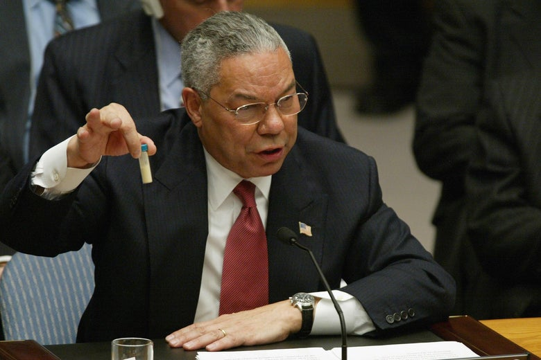 Colin Powell holds up a vial in front of a microphone, seated at the United Nations Security Council on Feb. 5, 2003.