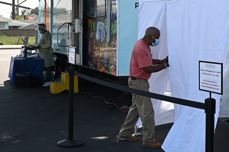 A man walks into a tent to be tested for COVID-19 at a mobile testing station in a public school parking area in Compton.