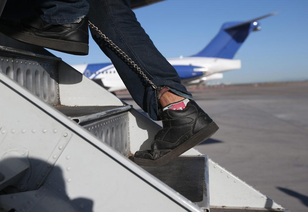 MESA, AZ - FEBRUARY 28:  A Honduran immigration detainee, his feet shackled and shoes laceless as a security precaution, boards a deportation flight to San Pedro Sula, Honduras on February 28, 2013 in Mesa, Arizona. U.S. Immigration and Customs Enforcement (ICE), operates 4-5 flights per week from Mesa to Central America, deporting hundreds of undocumented immigrants detained in western states of the U.S. With the possibility of federal budget sequestration, ICE released 303 immigration detainees in the last week from detention centers throughout Arizona. More than 2,000 immigration detainees remain in ICE custody in the state. Most detainees typically remain in custody for several weeks before they are deported to their home country, while others remain for longer periods while their immigration cases work through the courts.