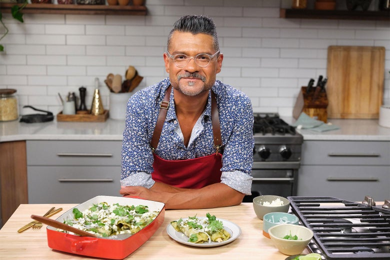 Rick Martinez in a beautiful kitchen, smiling over a casserole in a red dish.